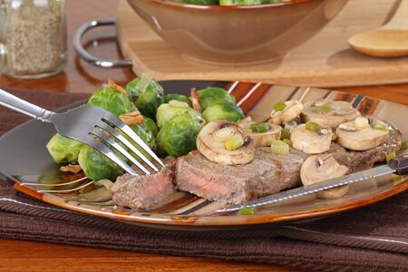 Cut piece of steak with mushrooms and brussels sprouts photo