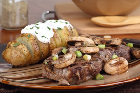 Steak covered with mushrooms and a baked potato