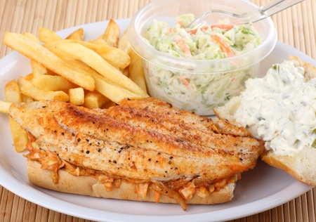 Carfish fillet sandwich with french fries and coleslaw photo