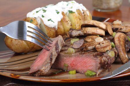 ステーキ キノコとサワー クリームとベイクド ポテトで覆われて 写真素材