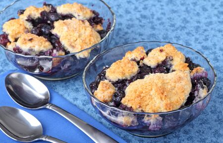 Two glass bowls of blueberry cobbler dessert