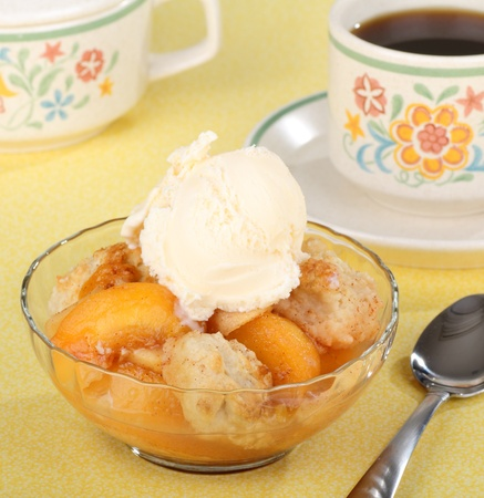 Bowl of peach cobbler with a scoop of ice cream and a cup of coffee