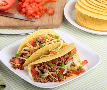 レタス、トマト、バック グラウンドでの食材を有する平板上にチーズと 2 つのタコス