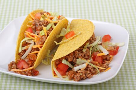 taco tortilla: Two tacos with lettuce, tomatoes, cheese on a plate