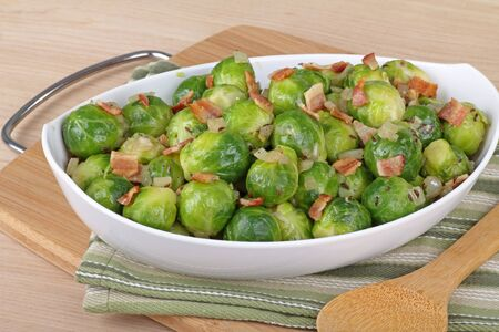 Cooked brussels sprouts with bacon pieces in a bowl Stock Photo