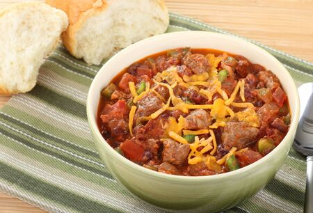 meat soup: Bowl of chili with cheese on top with bread in background
