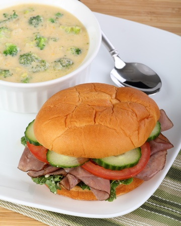 Roast beef sandwich with cucumber, lettuce, tomato and a bowl of soup photo