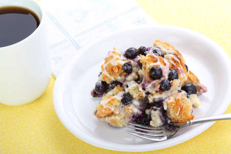 Plate of blueberry bread pudding with cup of coffee
