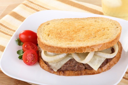 Sandwich with hamburger, onion, and cheese on rye bread with grape tomatoes on the side Stok Fotoğraf