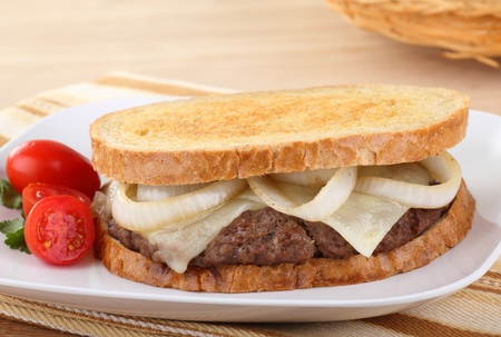 Sandwich with hamburger, onion, and cheese on rye bread with grape tomatoes on the side Banco de Imagens