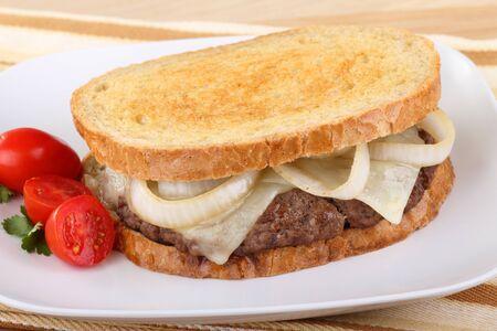 Sandwich con hamburguesa, cebolla y queso en pan de centeno con tomates uvas del lado
