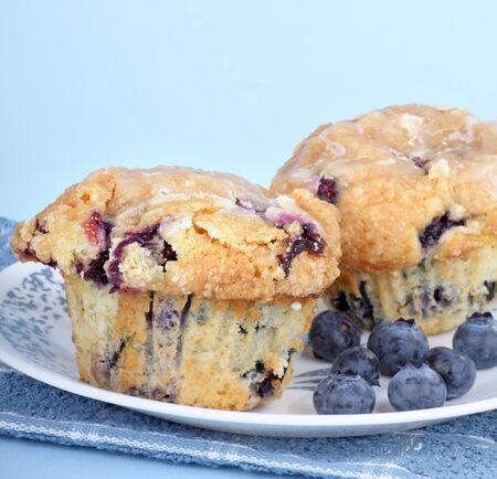 muffins: Blueberry muffins with blueberries on a plate with a blue background Stock Photo
