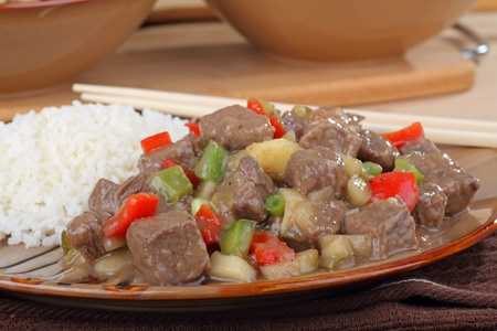 Closeup of sweet and sour beef with rice on a plate