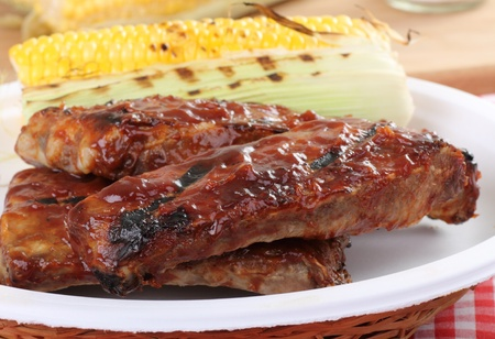 Grilled barbecue spareribs and ear of corn on a plate photo