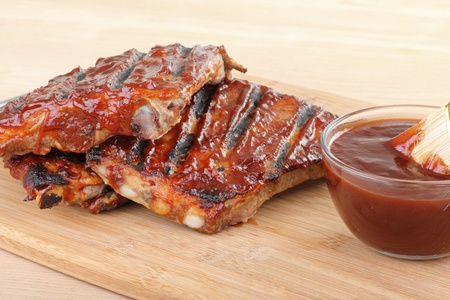 Grilled barbecue spareribs and barbecue sauce on a cutting board