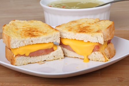 melted cheese: Grilled ham and cheese sandwich with soup in the background