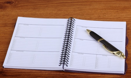 Opened weekly planner with a pen on a desk top