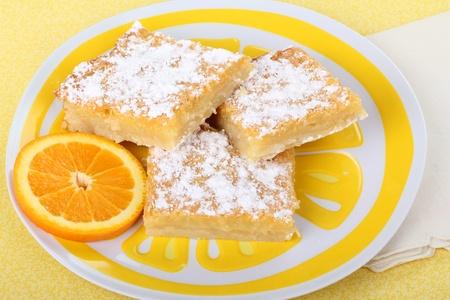 Orange bar dessert on a plate with an orange slice