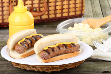 Two grilled bratwurst on buns with mustard on a picnic table