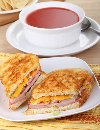 Grilled ham and cheese sandwich on a plate with tomato soup