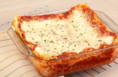 Baked lasagna in a baking dish on a cooling rack photo