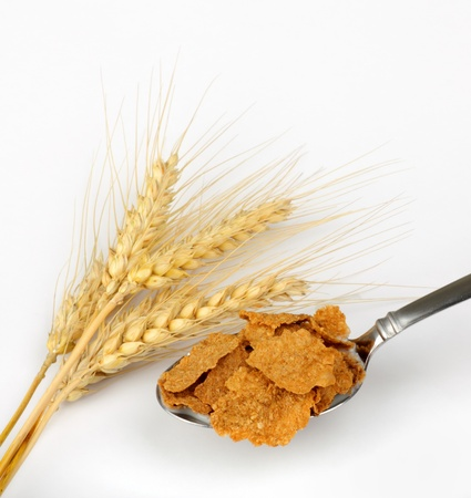 cuiller�e: Wheat heads next to a spoonful of wheat cereal flakes on a white background