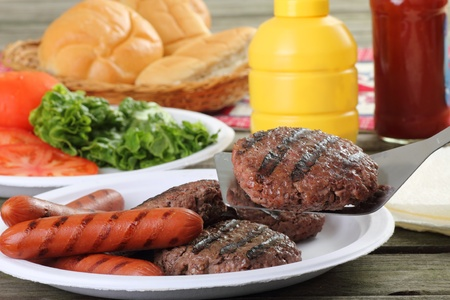 Grilled hamburgers, with one on a spatula, and hotdogs on a picnic table Фото со стока