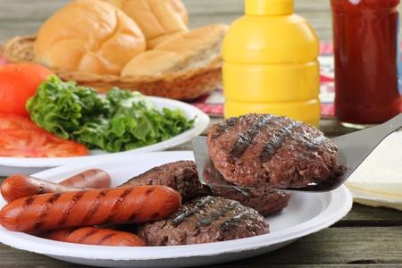 perro caliente: Hamburguesas a la parrilla, con uno en una esp�tula y perritos calientes en una mesa de picnic