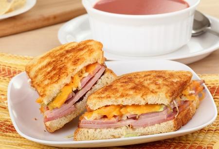 jamon y queso: Sándwich de jamón y queso a la parrilla con un tazón de sopa
