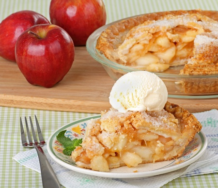 Slice of apple pie on a plate with apples and a pie in the background Stock Photo