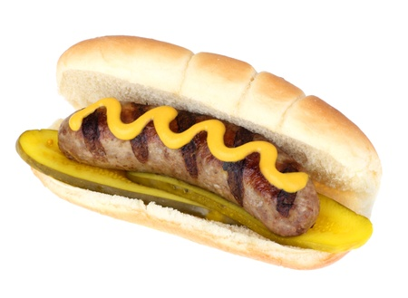 Grilled bratwurst with mustard and pickles on a bun isolated on white