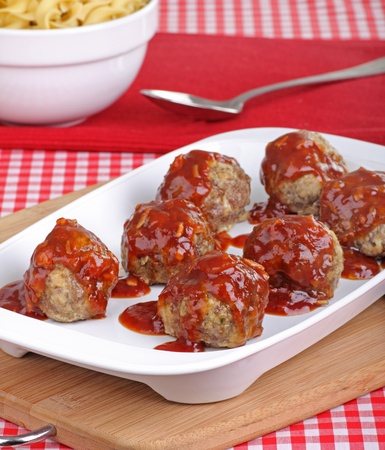 Meatballs covered with sauce and noodles on a platter Stock Photo