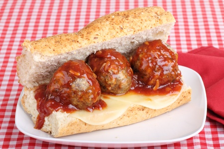 Meatballs covered with sauce and cheese on a bun