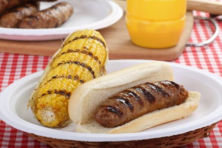 Grilled bratwurst on a bun with corn on the cob