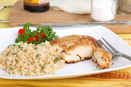 Breaded chicken breast meal with brown rice on a plate