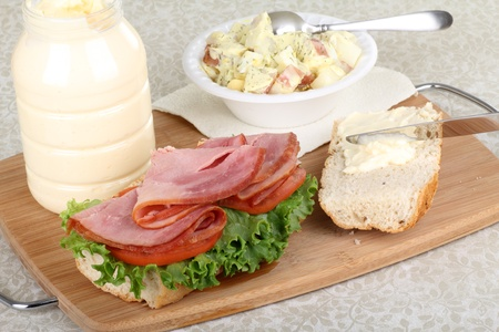 Spreading mayonnaise on a bun for a ham sandwich with lettuce and tomato