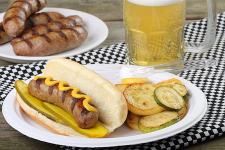 bratwurst: Grilled bratwurst with mustard and pickles on a bun Stock Photo
