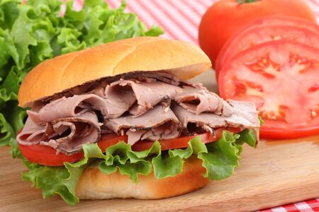 Closeup of a roast beef sandwich with lettuce and tomato