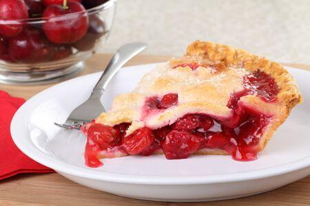 バック グラウンドでチェリーと皿の上の桜のパイのスライス 写真素材