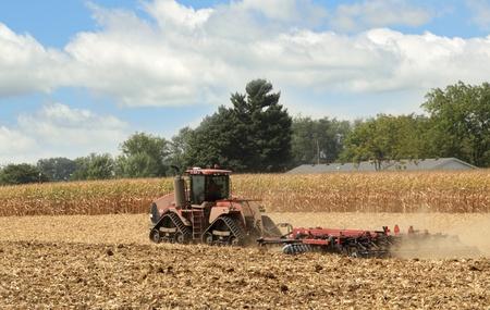 arando: Tractor rojo arando un campo agrícola Foto de archivo