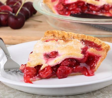チェリーと皿の上の桜のパイとバック グラウンドで全体パイのスライス
