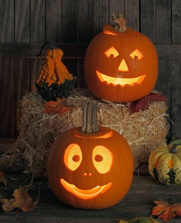 Two smiling jack-o-lanterns one on a wood floor and one on a straw bail Stock Photo