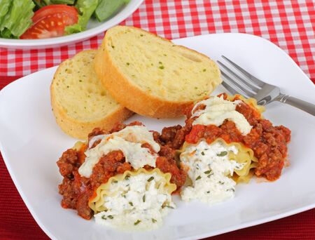 lasagna: Two baked lasagna rolls with bread on a plate