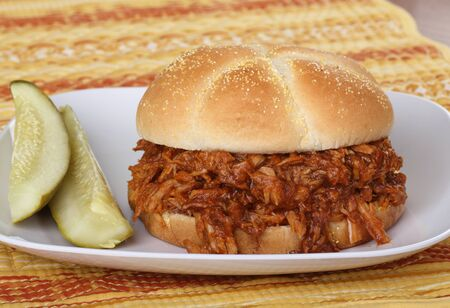 Barbecue pulled pork sandwich on a bun with two pickles Stock Photo