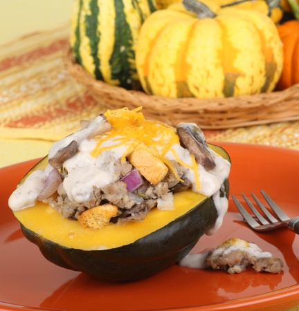 Stuffed squash on a plate with basket of squash in background