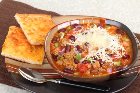 Bowl of chili with beans and cheese bread on the side