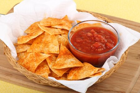 Spicy tortilla chips and salsa in a basket Stock Photo