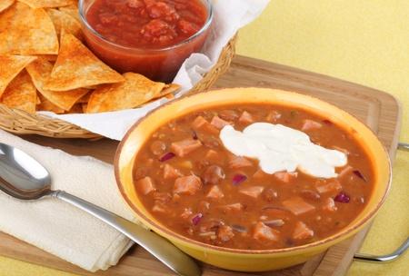 バック グラウンドでサルサとトルティーヤ チップ サワー クリームとハムと豆のスープのボウル 写真素材