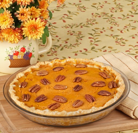whole pecans: Whole pumpkin pie with pecans on a tray
