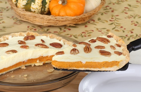 Slice of pumpkin cheesecake pie with pecans on a spatula